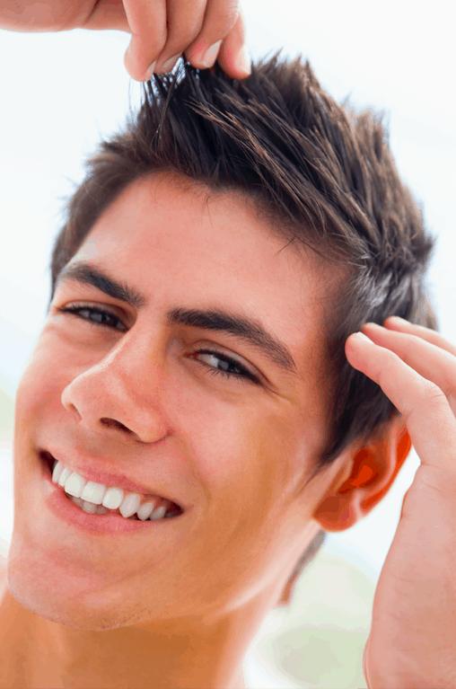 man grooming his hair with hair cream