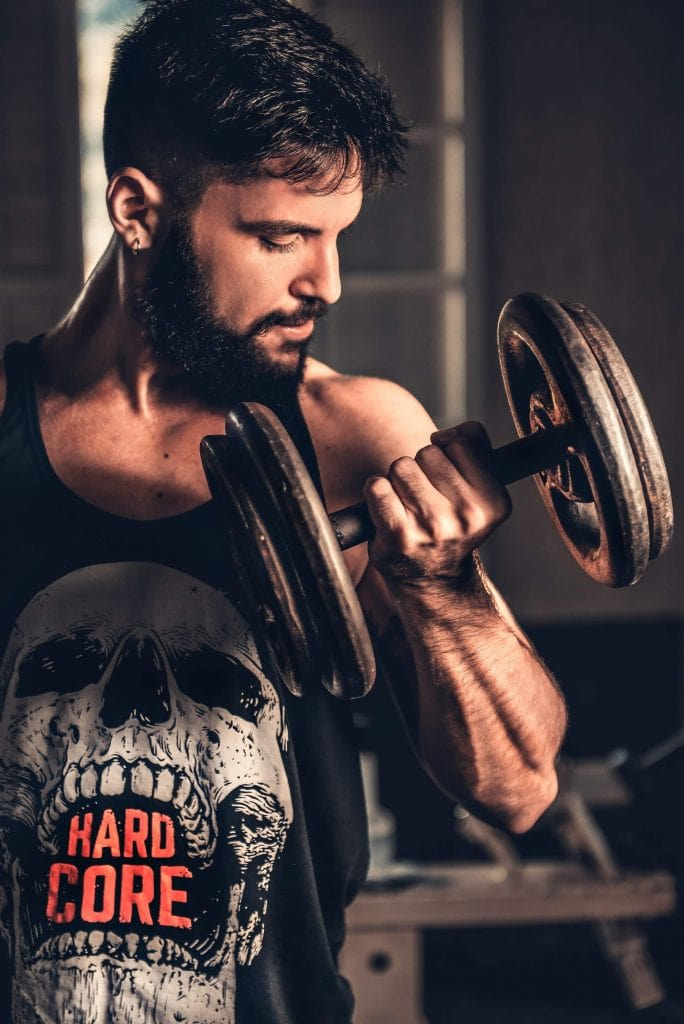 Man working out with dumbbells and a T-shirt that says hardcore