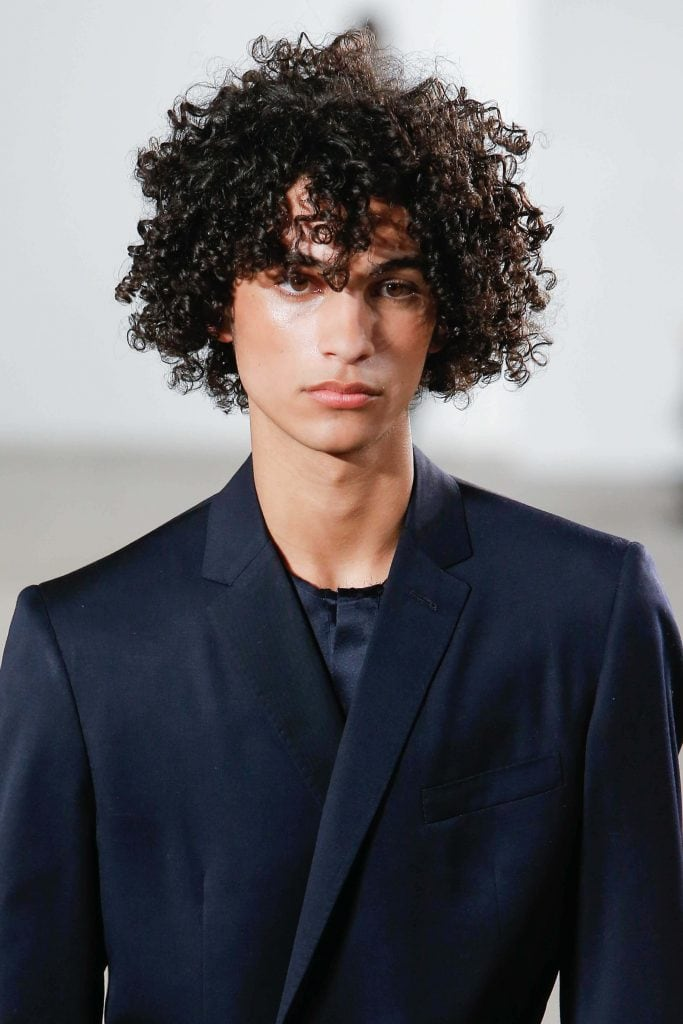 man with long curly hair in a black suit