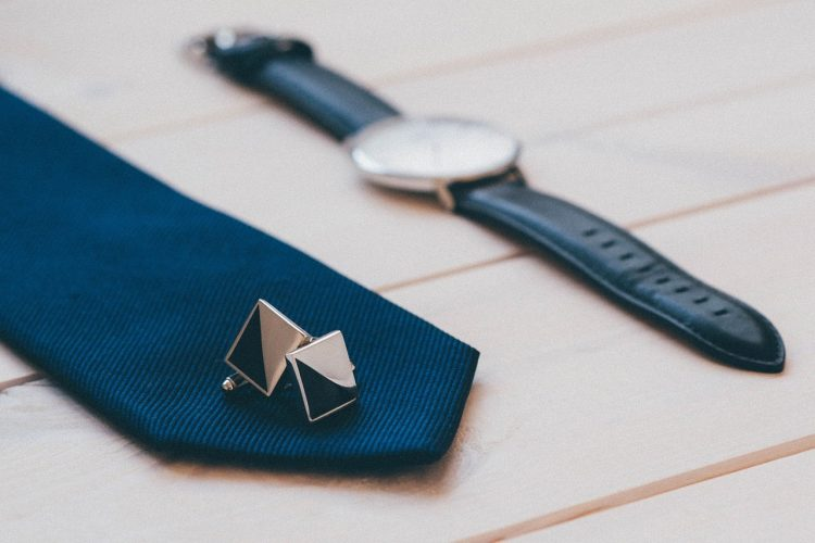A navy tie with cufflinks and a watch