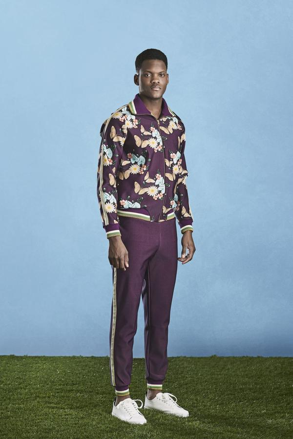A man wearing a purple floral jacket with matching purple jogger sweatpants. - jogger outfits  men