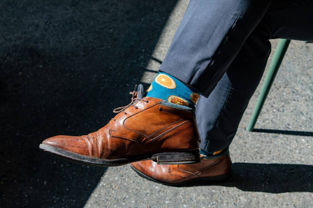man wearing blue pants and brown shoes