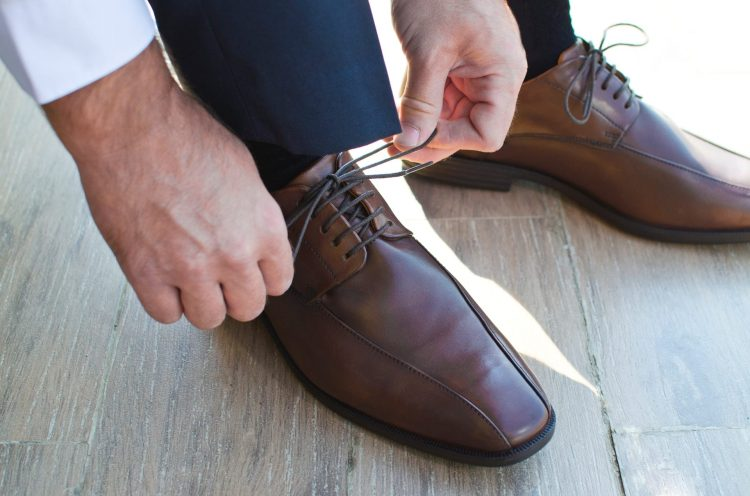 men tying the cords of brown shoes