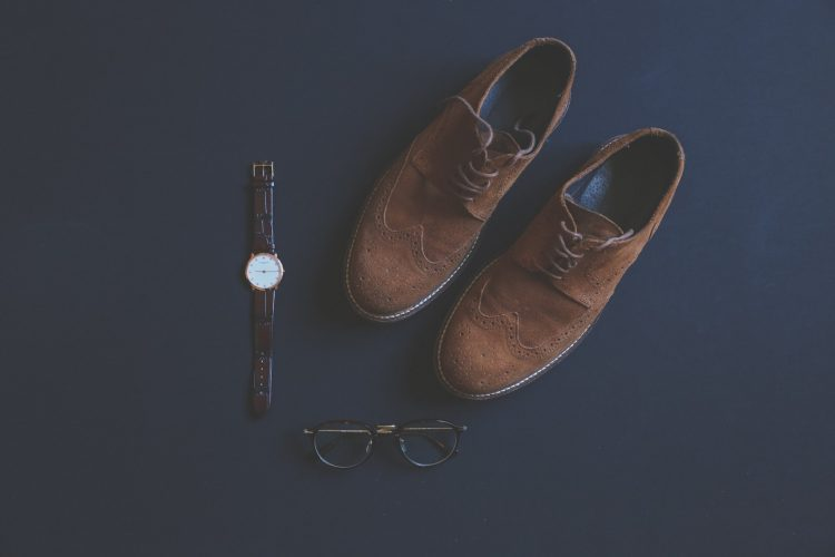 brown shoes, a brown watch, and black glasses