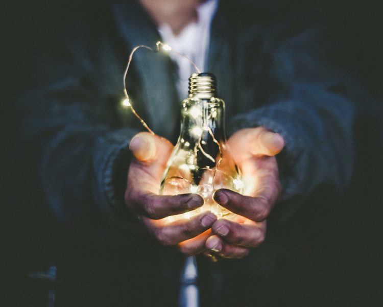 Man with dirty hands holding a light bulb with both hands