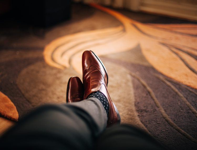 Man with dress shoes laying on rug