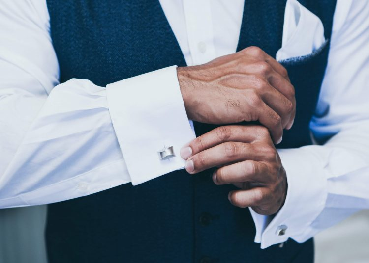 man holding his sleeve with cufflinks