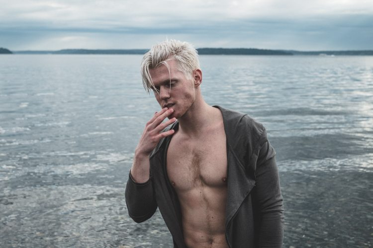 man with wet blonde hair at the beach