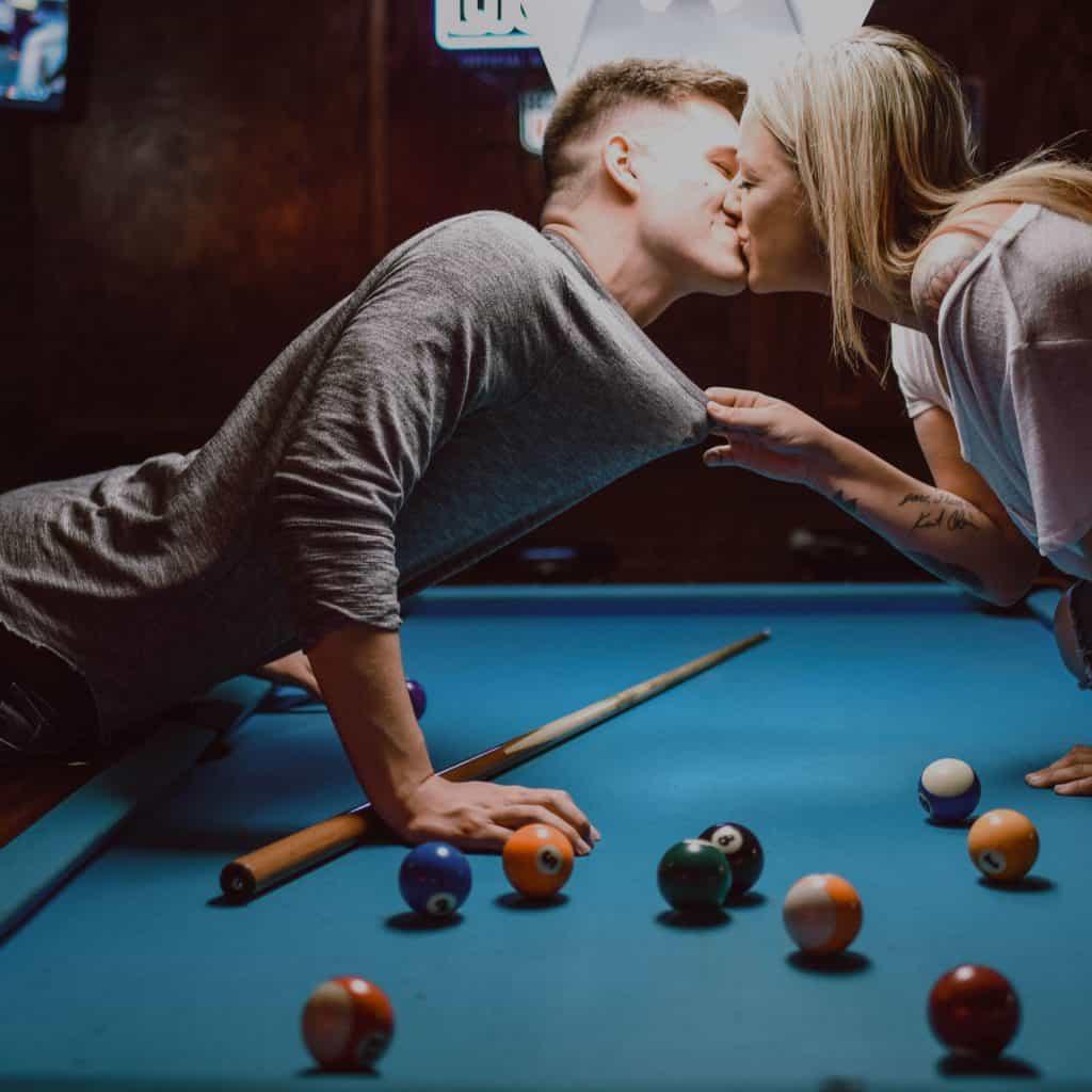 clean shaven man kissing a tattooed woman