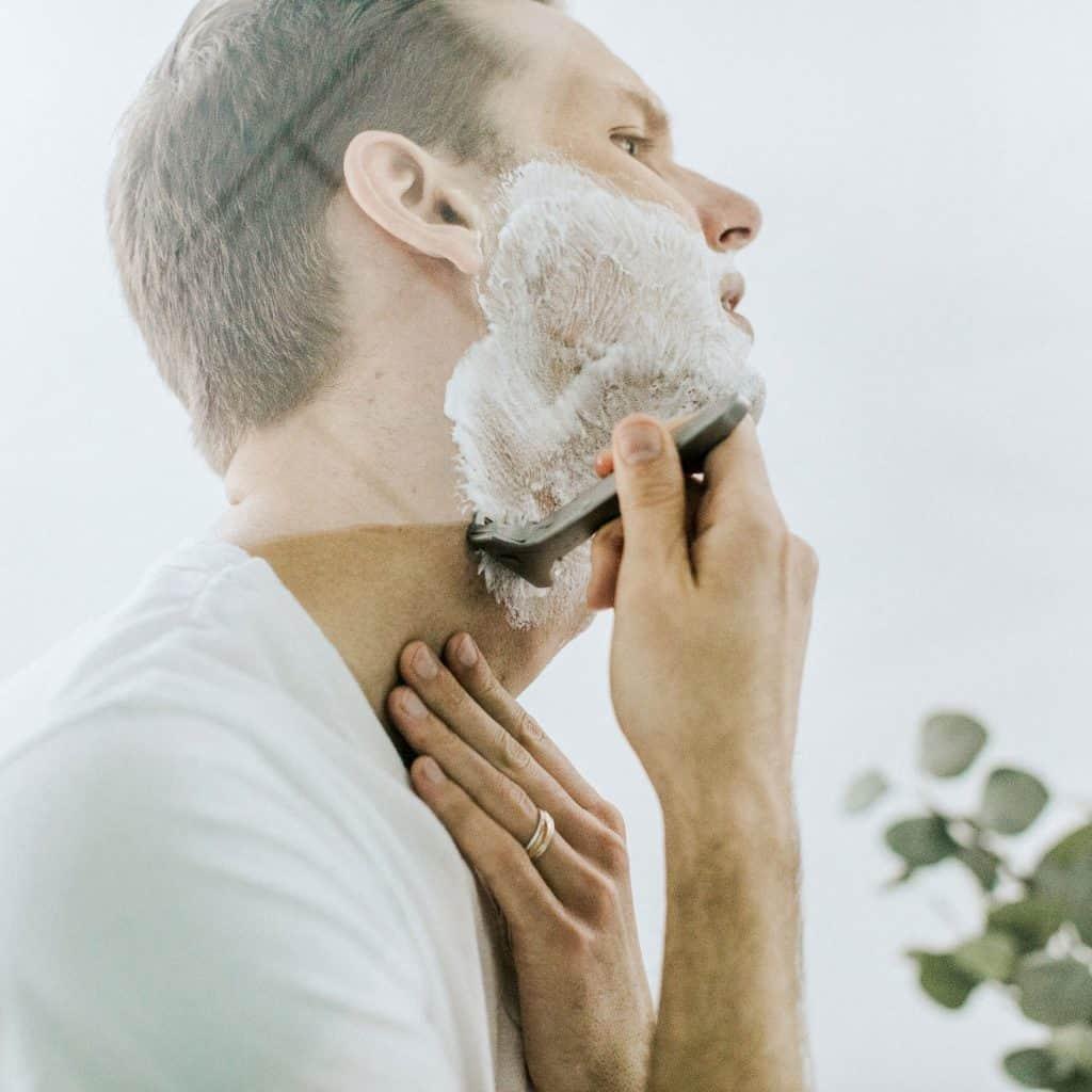 man shaving his beard using shaving cream