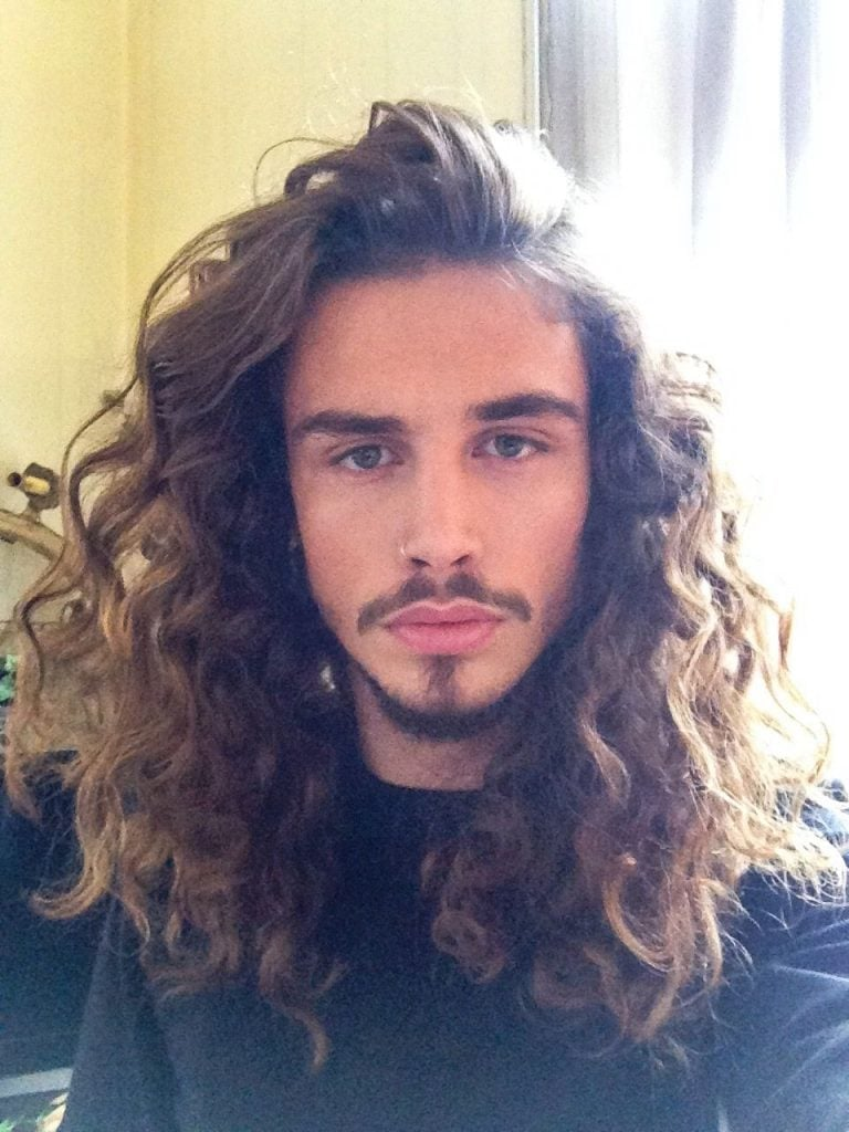 man with long curly hair and a goatee