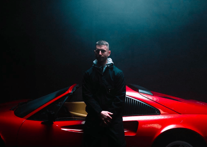 Marc E. Bassy in front of a sports car
