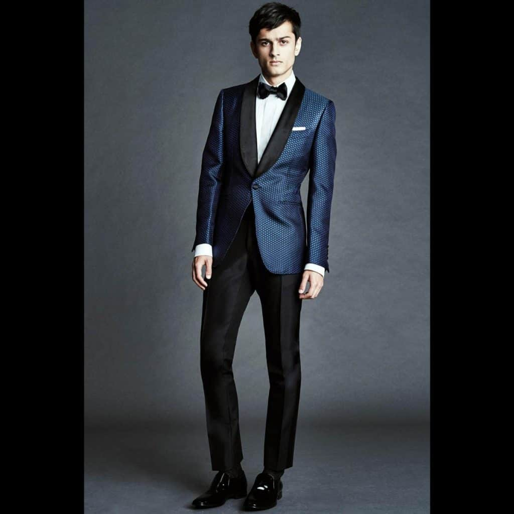 A man wearing a blue cocktail suit with black pants from Tom Ford