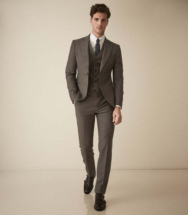Man wearing a brown Reiss cocktail suit