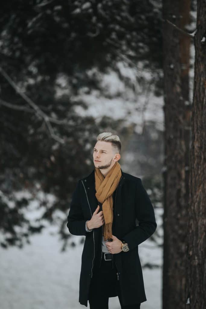 A man in the woods with a coat and scarf