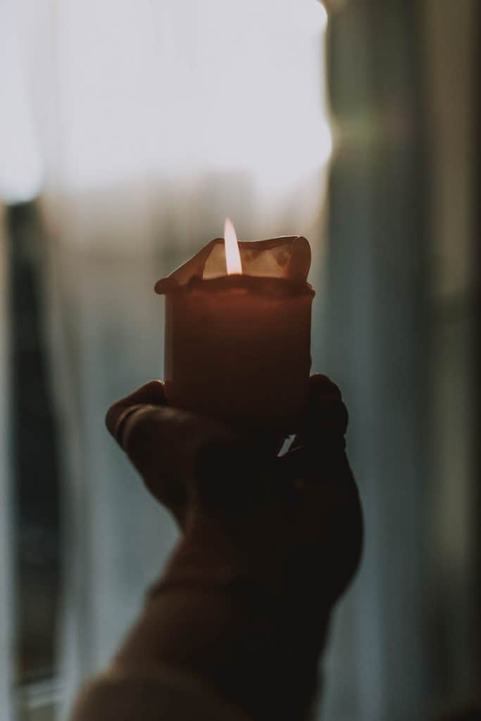 person-holding-lighted-candle-in-dark-room