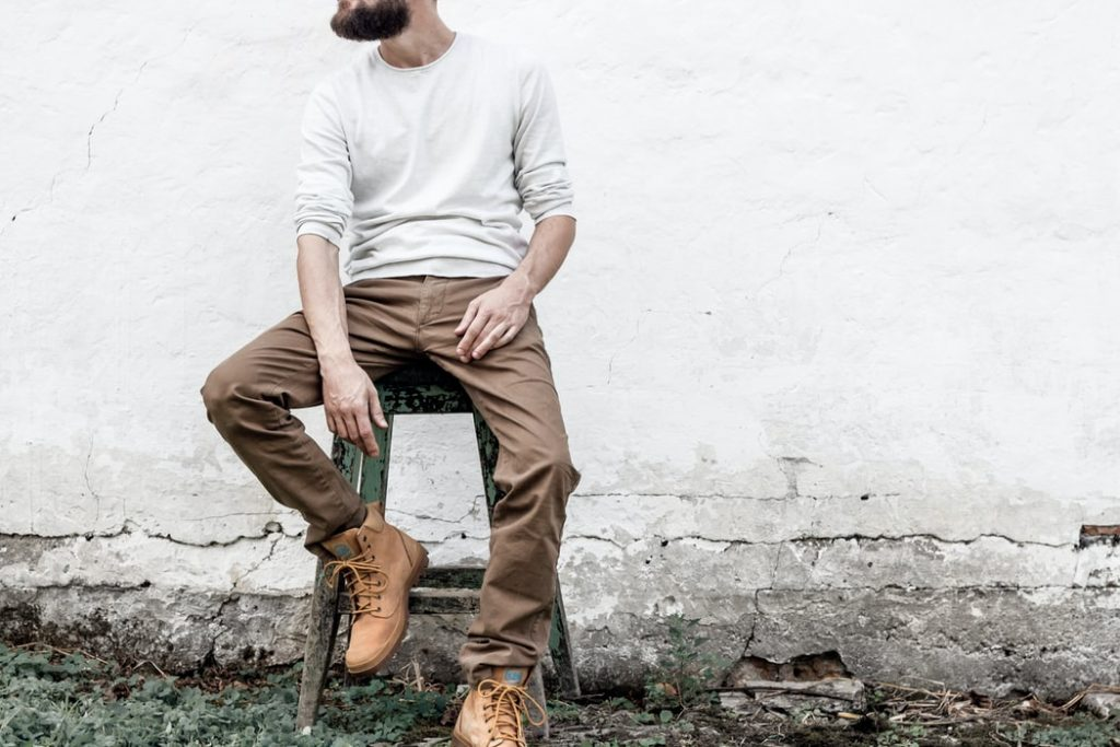 A photo of a man sitting wearing a boots
