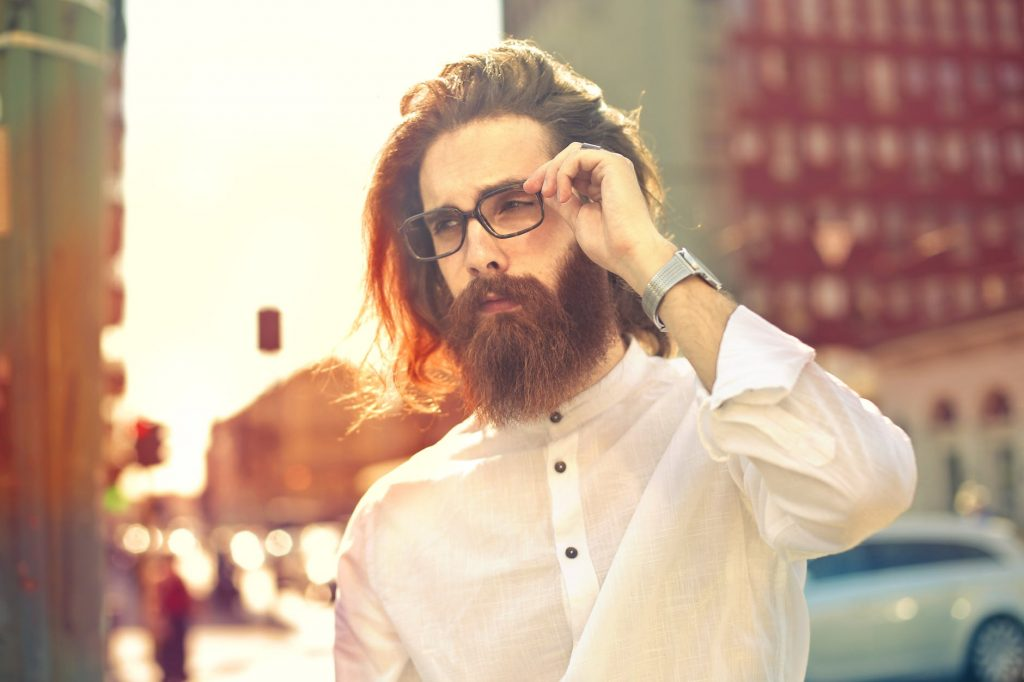 Photo of a beard man in white dress shirt wearing eyeglasses
