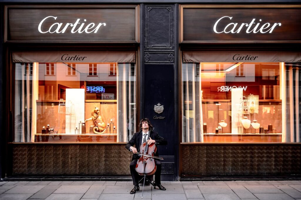 Man sitting in front of Cartier shop waiting for Men Fragrances